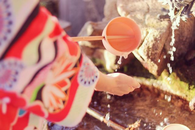 初詣の前に手水舎でお清めをする女の子