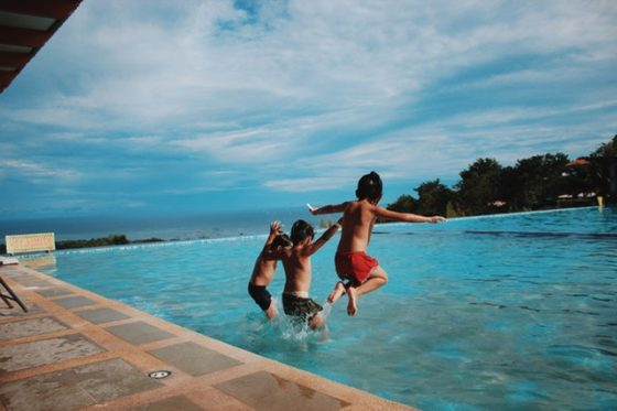 子供達がプールにジャンプ